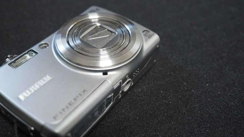 FujiFilm FinePix F100fd の写真。カメラ本体が斜めに映し出されている。レンズ部分に注目して映し出されている。