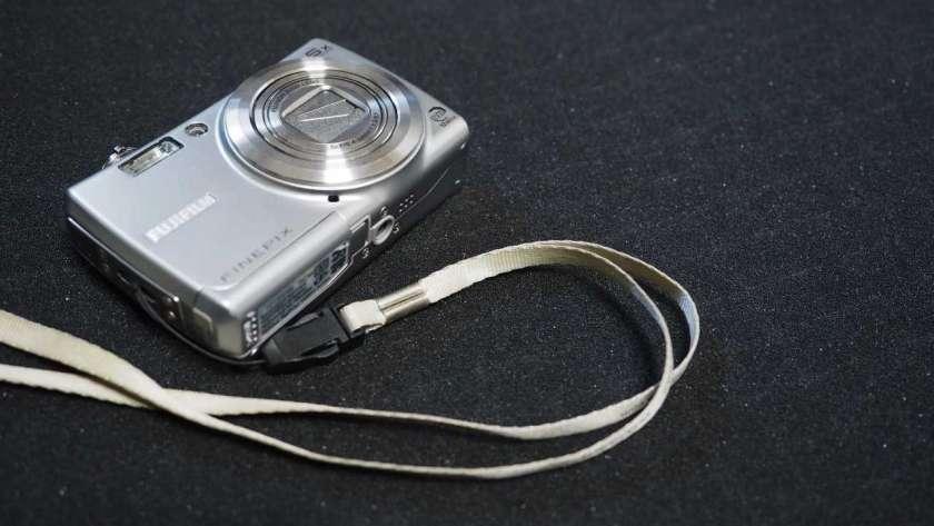 FujiFilm FinePix F100fd の写真。カメラ本体はやや小さく映し出されているがストラップも映している。